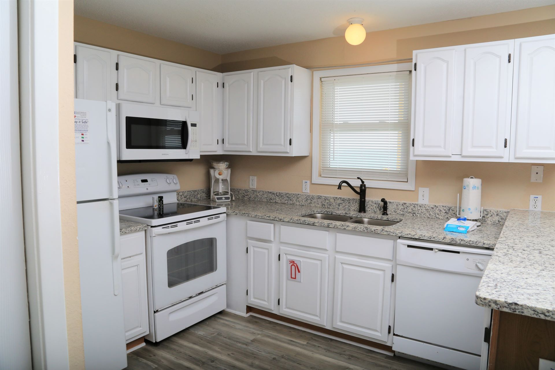 The kitchen includes matching white appliances and is stocke