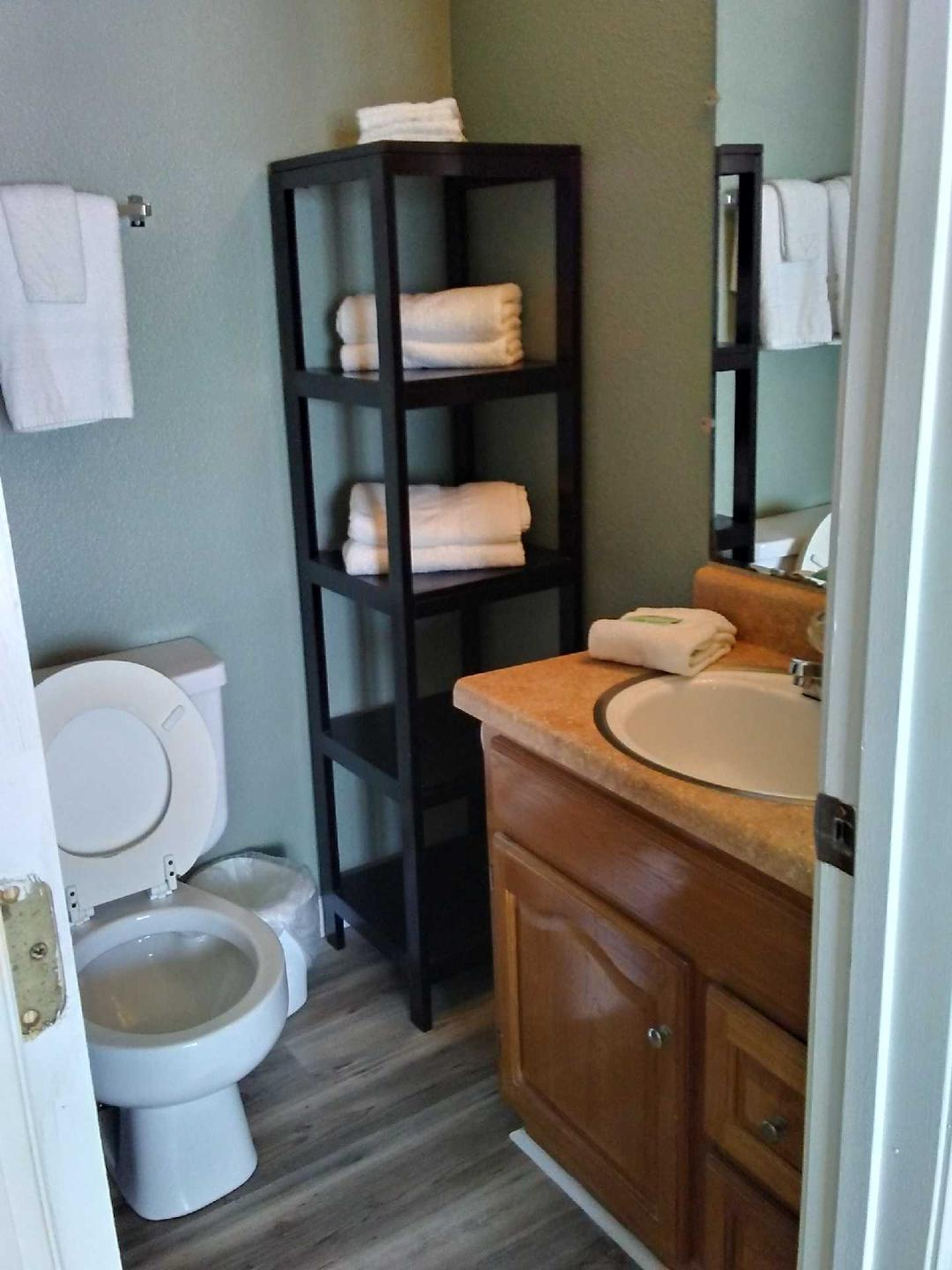 The bathroom with shower/tub combo and shelves for storage