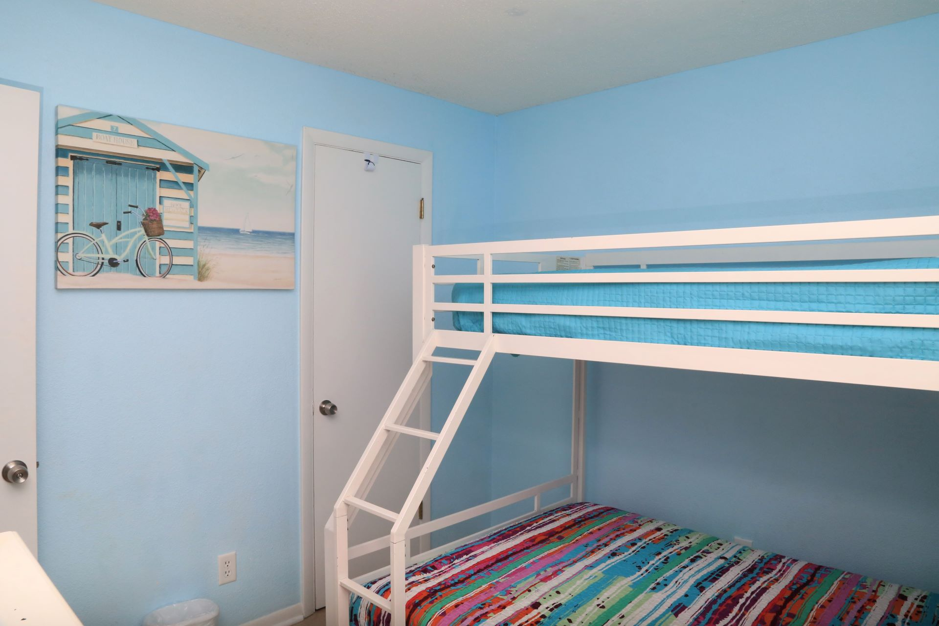 Bunk room includes a closet and dresser for storage.