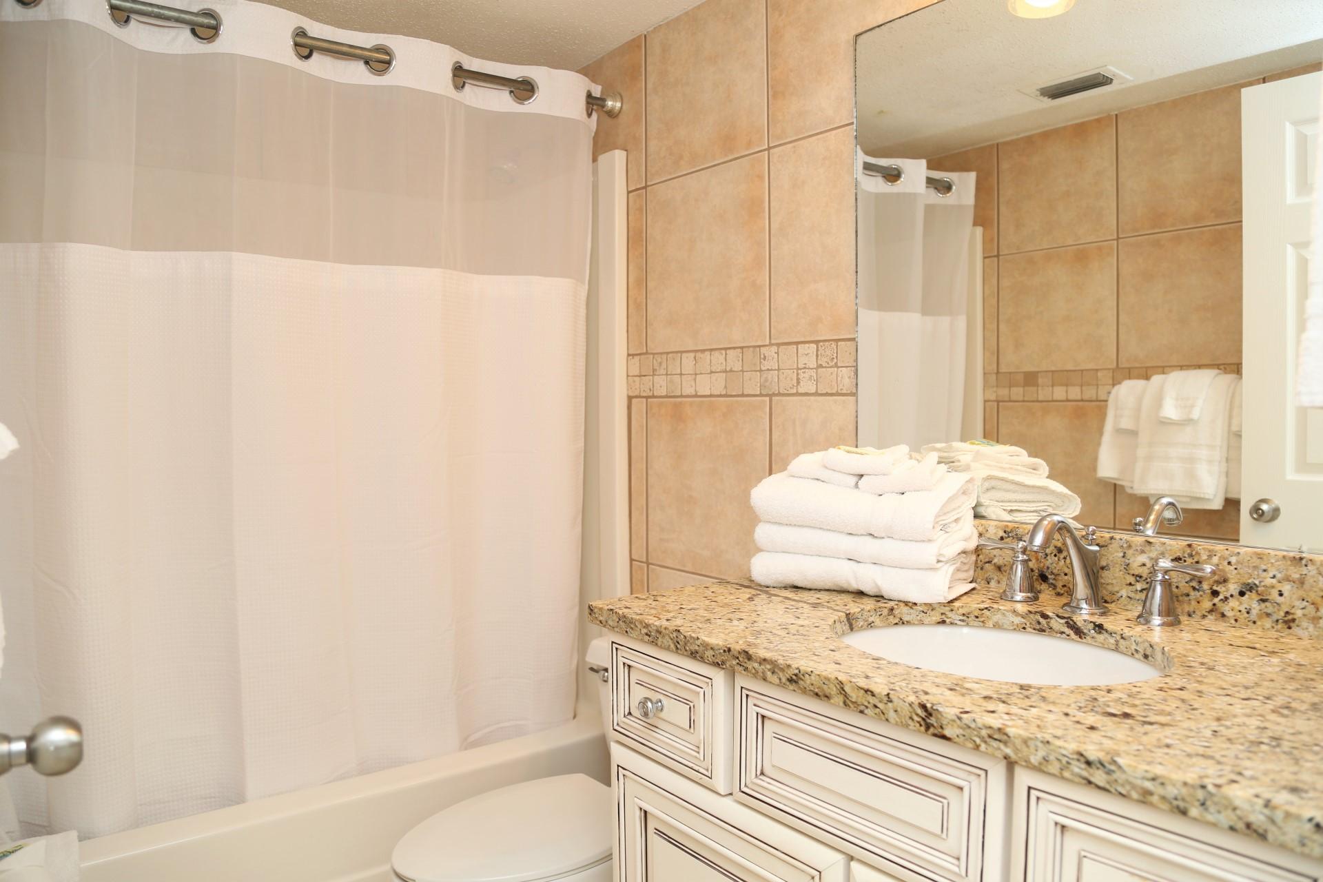 Hallway bathroom - shower/tub combo with granite countertop