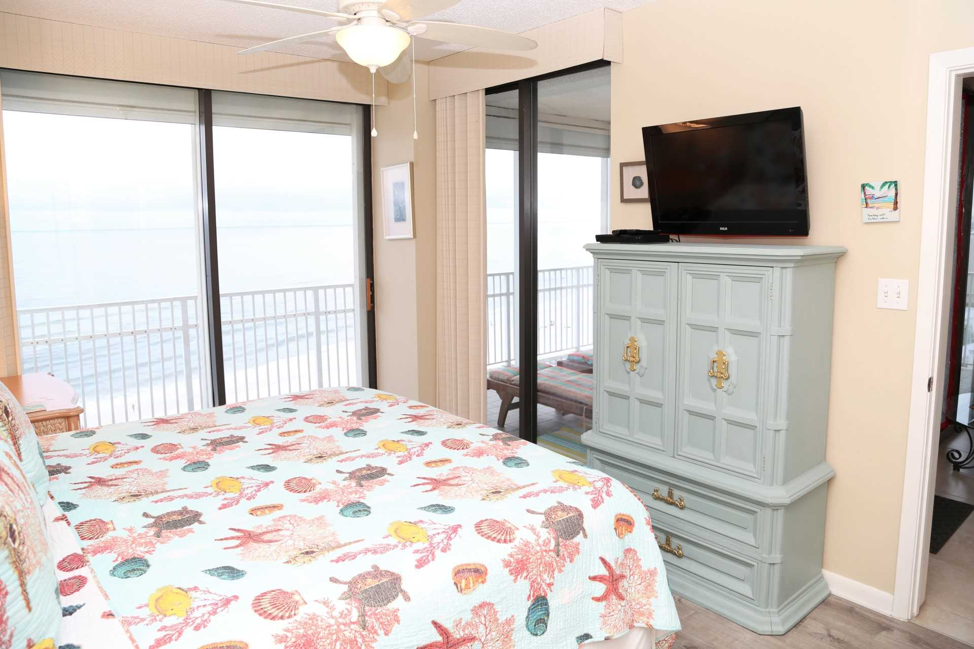 The master bedroom with cable TV, dresser, and access to bal