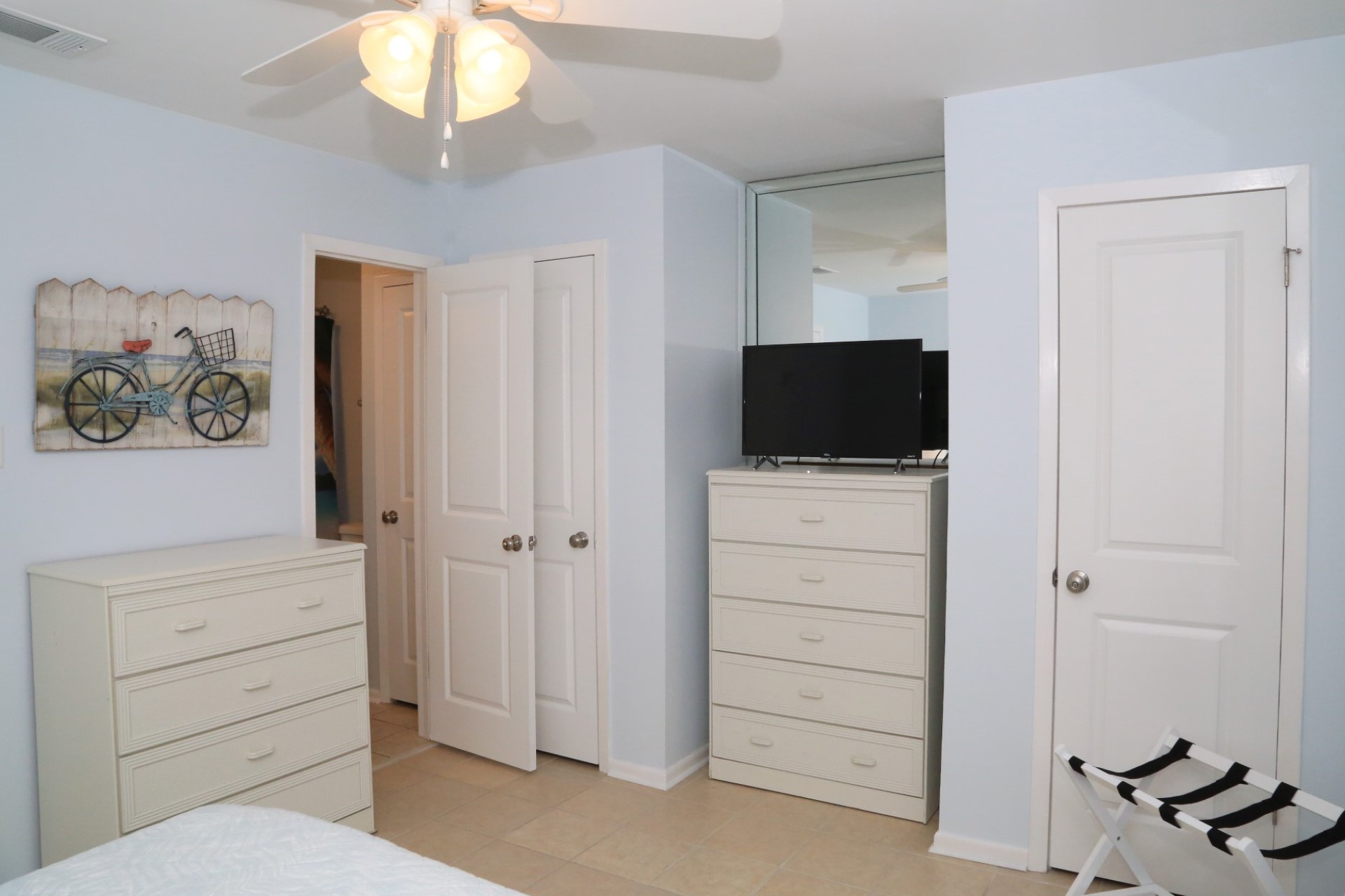 The master bedroom with TV, dressers, and bathroom.