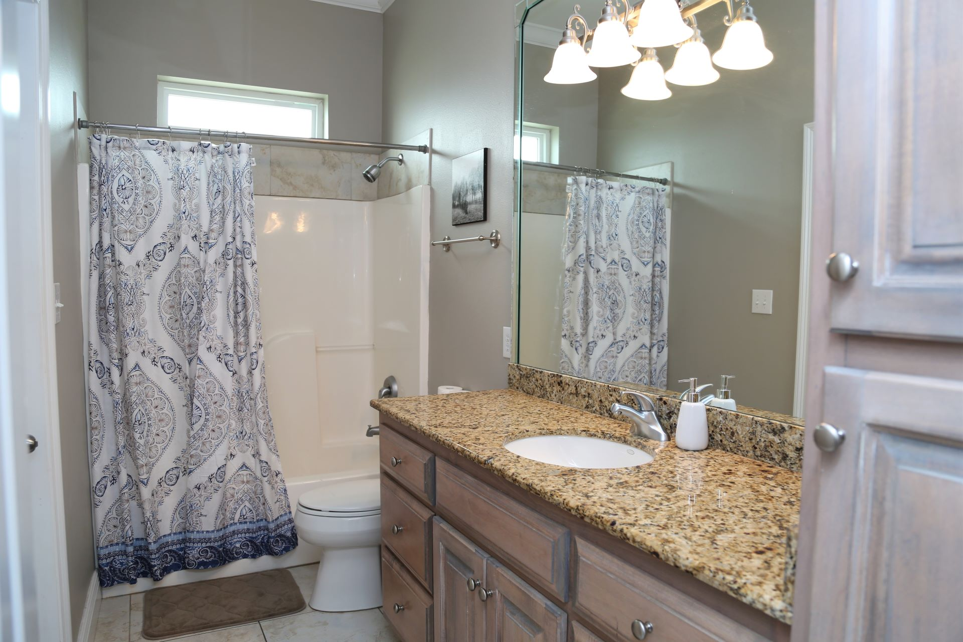 The hall bathroom with shower/tub combo, large vanity, and c